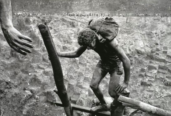 A miner carries his load to the top of the Serra Pelada gold mine, Brazil. Image (c) Sebastiao Salgado.