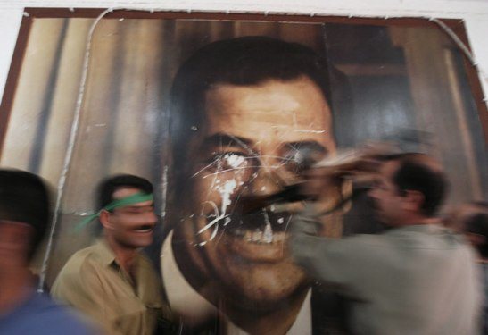 Hours after the fall of Kirkuk in 2003, Kurdish Peshmerga soldiers deface a poster of Saddam Hussein in a government building. Lynsey Addario/Getty Images Reportage
