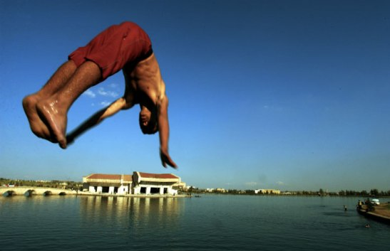 A boy dives into the water at a former palace of Saddam Hussein, Mosel, Iraq, 2003. Lynsey Addario/Getty Images Reportage