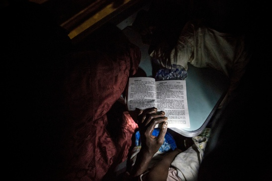 A woman reads a Hausa romance novel using the flashlight on her cell phone on a train crossing Nigeria. Image (c) Glenna Gordon
